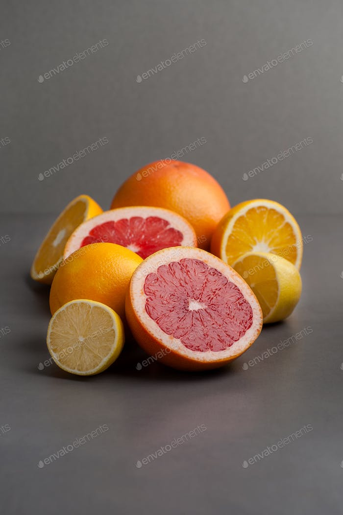 Grapefruits, oranges and lemons on a gray background.