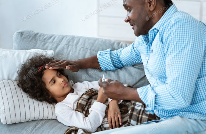 Infectious disease. Cute African American girl suffering from fever and caring grandfather next to