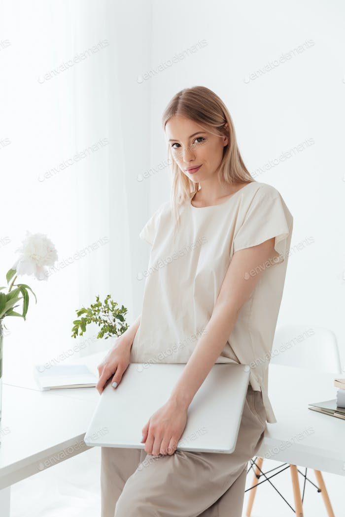 Lady standing indoors holding laptop computer.