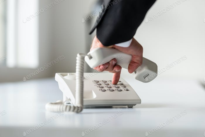 Male hand dialing a telephone number in order to make a phone ca
