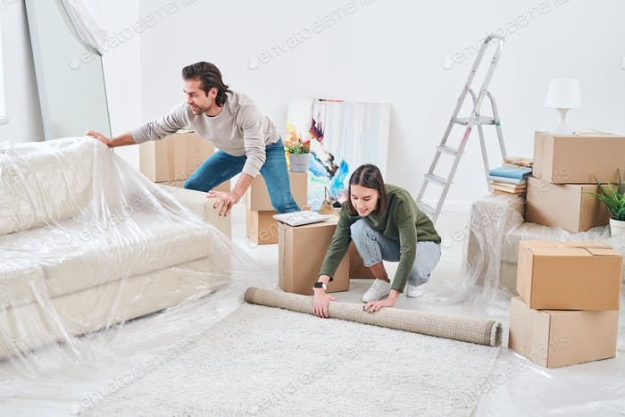 Young woman rolling rug on the floor and her husband putting cellophane on couch