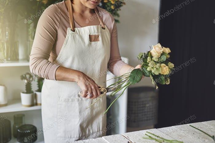 Female florist working in her flower shop trimming a bouquet