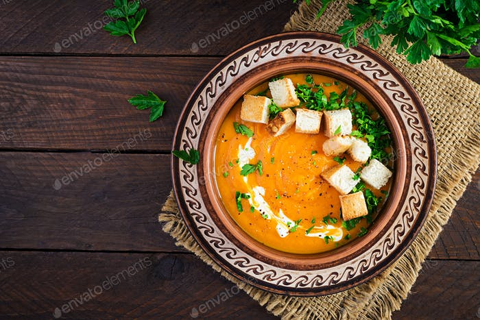 Kürbissuppe in einer Schüssel serviert mit Croutons und Petersilie. Vegane Diät-Suppe.