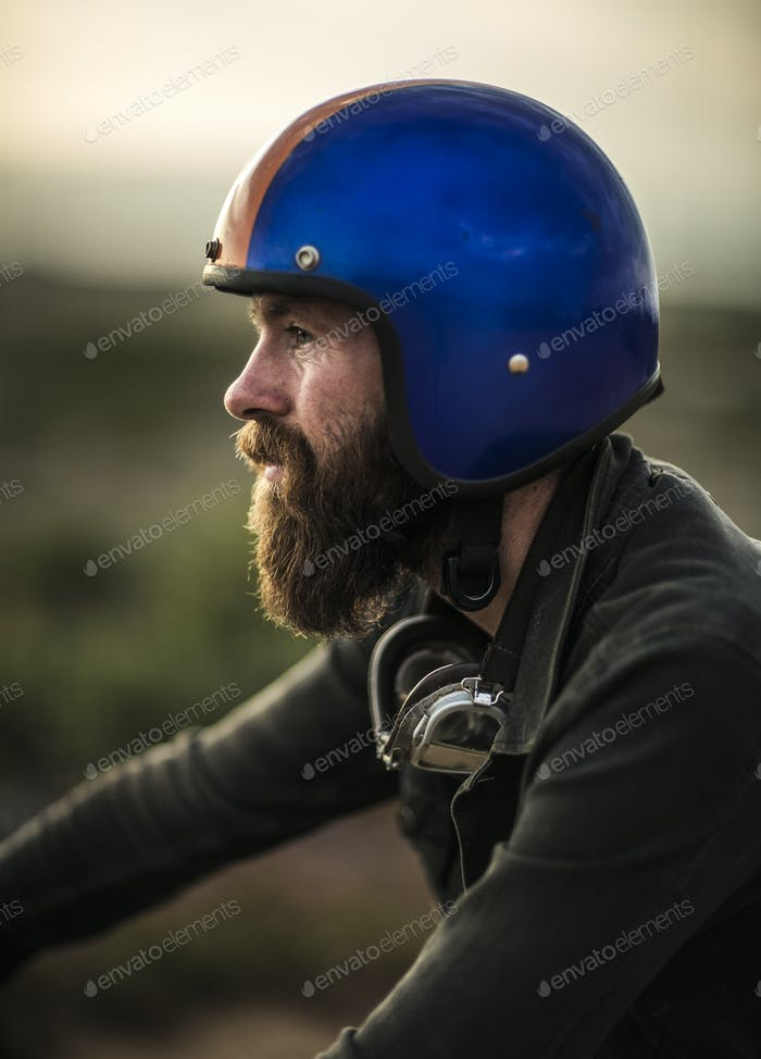 Profile of bearded man wearing blue open face crash helmet, goggles round his neck.