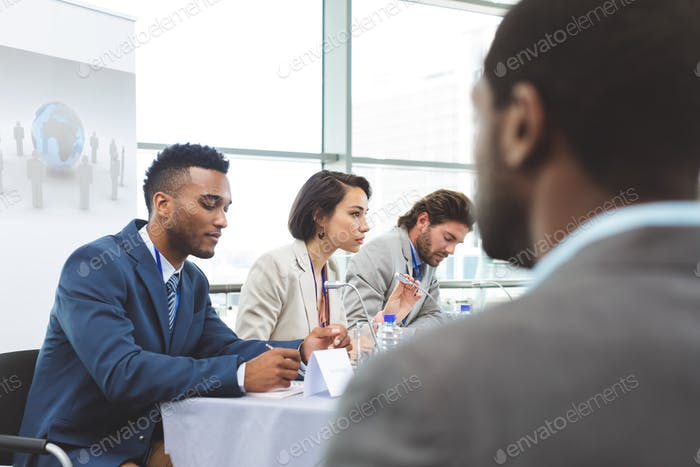 Side view of mixed race business people sitting at table in seminar