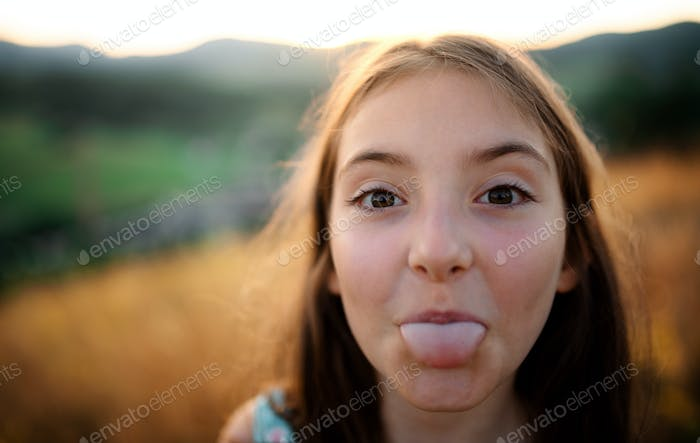 A portrait of small girl in in nature, sticking out tongue.