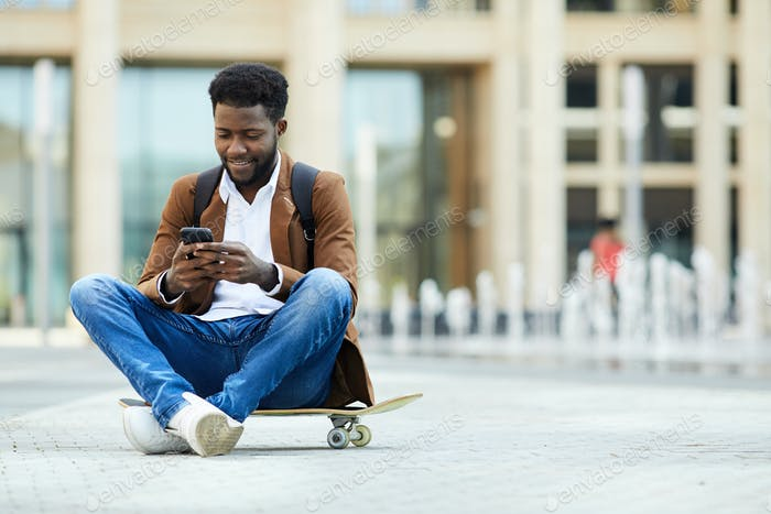Young African-American Man Texting in City Square