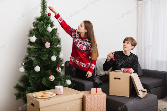 Beautiful young couple sitting on sofa at home and dreamily decorating Christmas tree together