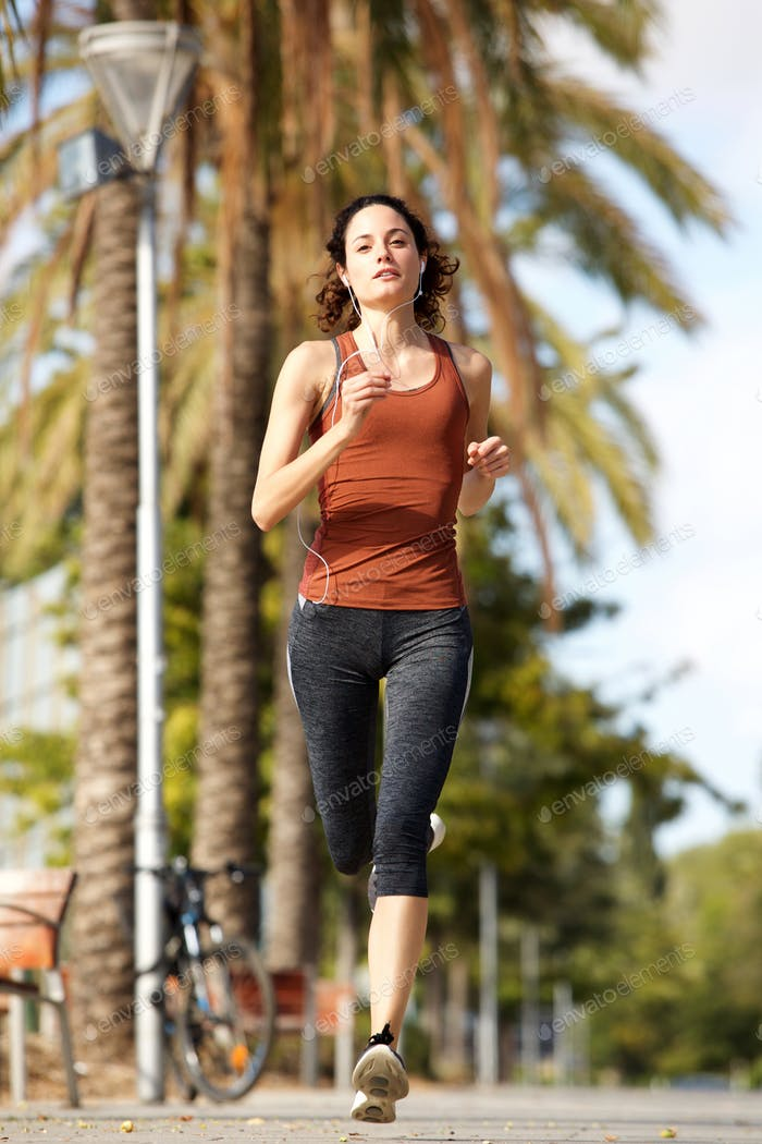 Full body young woman running outdoors