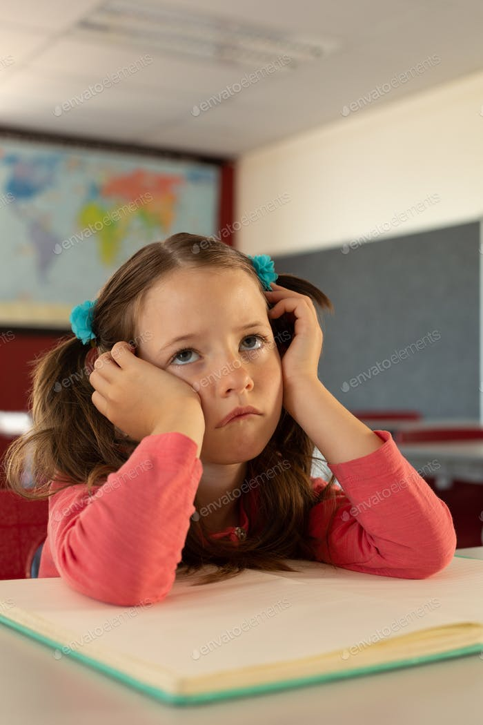 Front view of thoughtful sad Caucasian girl leaning on desk in a classroom at elementary school