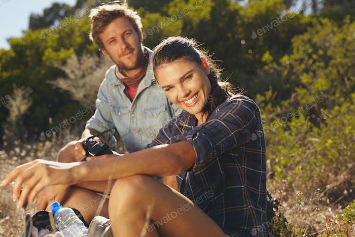 Happy couple taking a break on hike