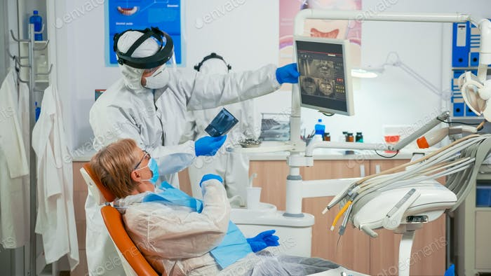 Stomatologist in protective suit explaining dental radiography