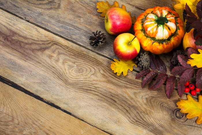 Thanksgiving background with cones, apples, pumpkin on wooden ta