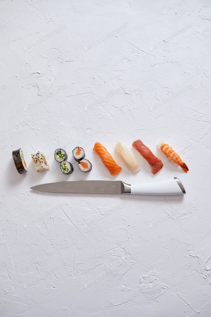 Various sushi rolls with Japanese knife on white stone slate background