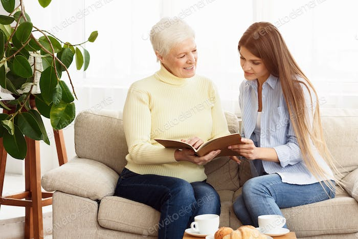 Elderly woman looking family album with her daughter