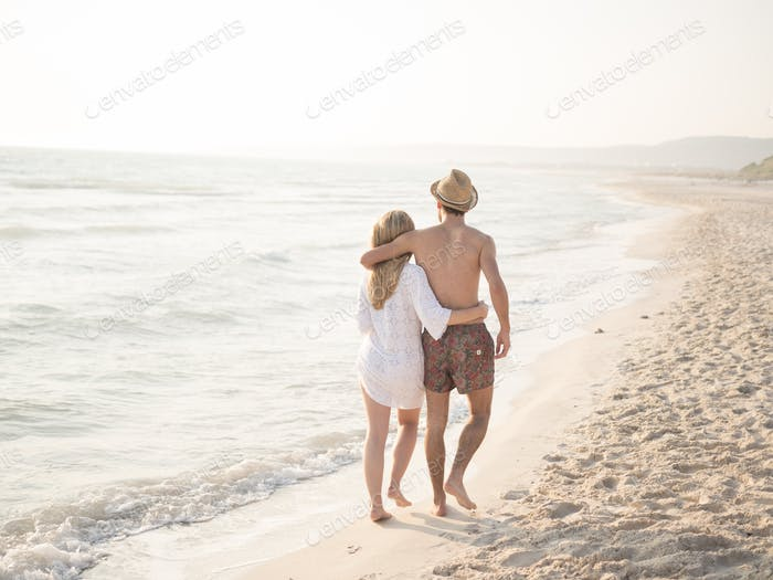 Young couple in love on a white beach at sunset