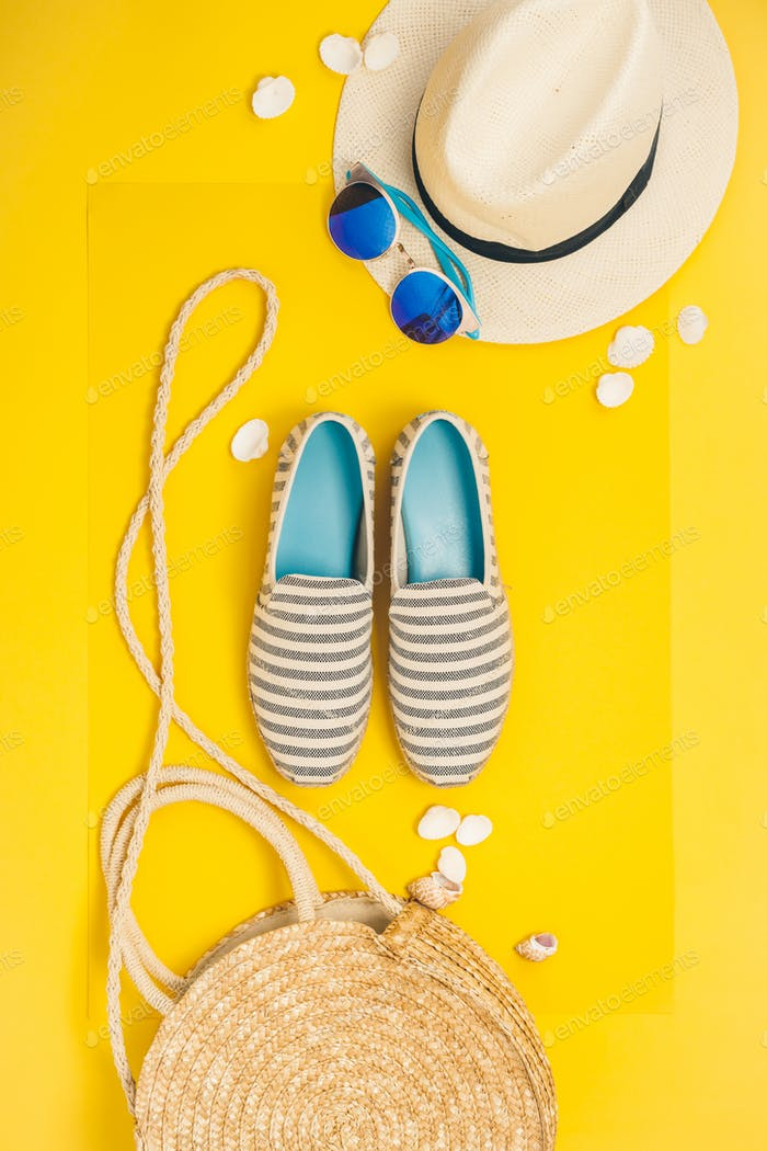 Flat lay traveler accessories on yellow background with straw hat, summer shoes, bag and sunglasses