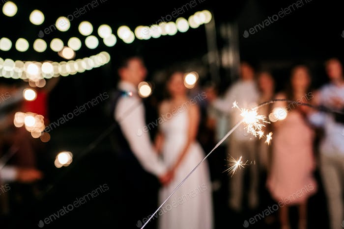 sparklers at the wedding, a couple of newlyweds on the background
