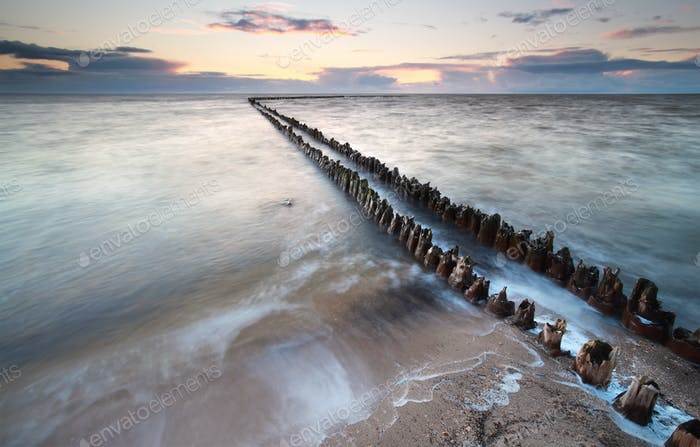 old breakwater in sea waves at sunset