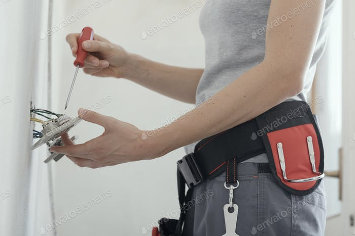 Female electrician fixing a socket at home