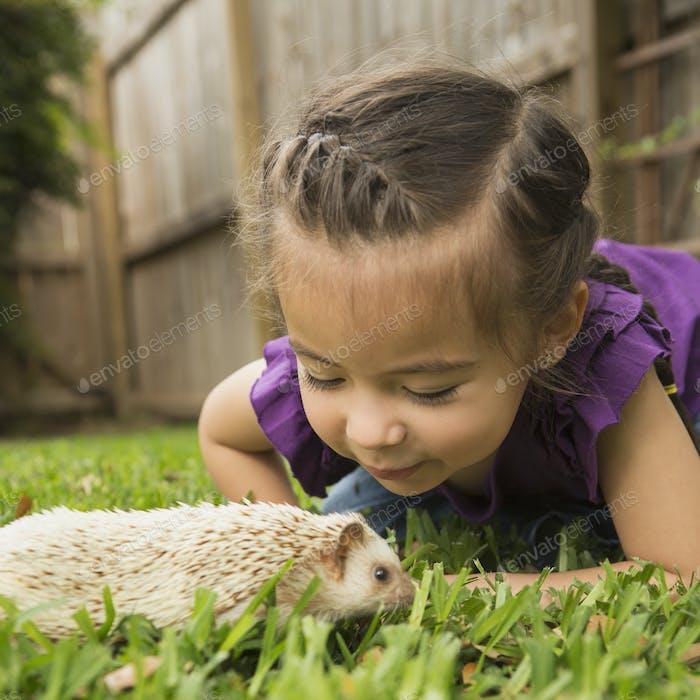 Ein junges Mädchen auf dem Gras, das einen kleinen Igel ansieht.