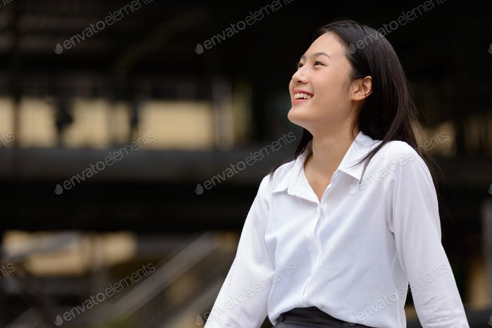 Young beautiful Asian businesswoman in the city outdoors