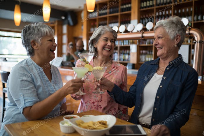 Senior female friends toasting glass of cocktail in bar