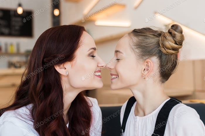 beautiful mother and daughter touching noses