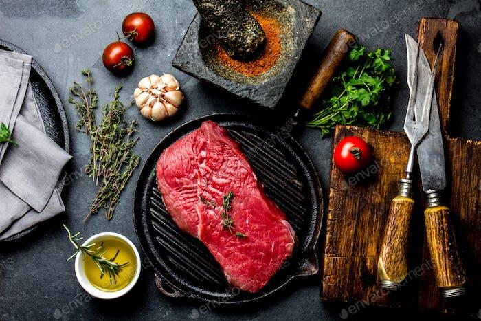 Fresh raw meat steak beef tenderloin, herbs and spices around cutting board.