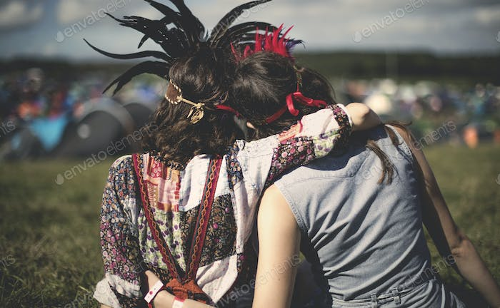 Rear view of two young women at a summer music festival wearing feather headdresses, arm around