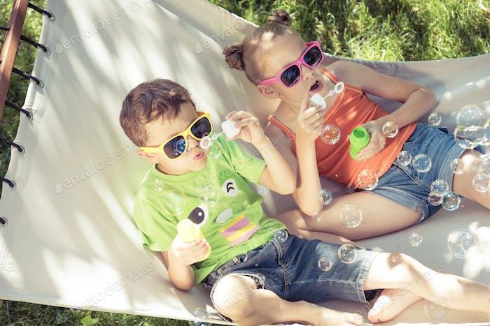 Zwei glückliche Kinder liegen auf einer Hängematte und spielen mit Seifenblasen