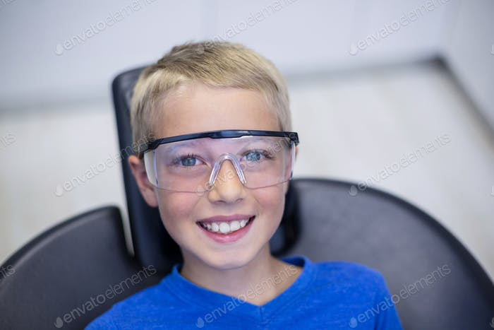 Smiling young patient sitting on dentist chair