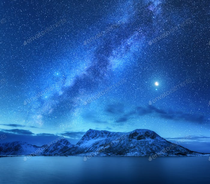 Milky Way over snow covered mountains and sea at night in winter