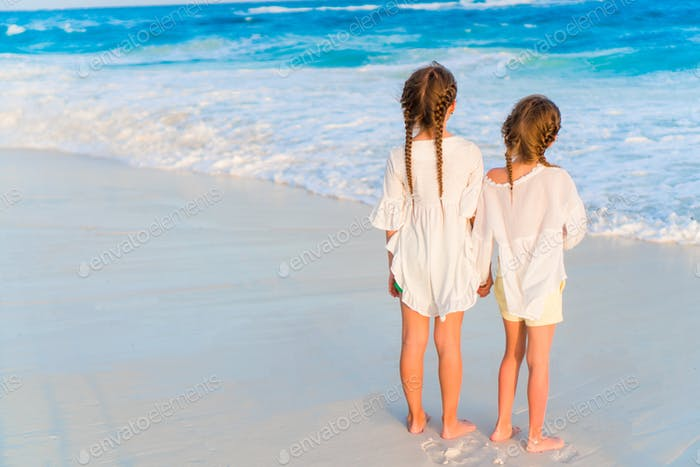 Adorable little sisters together on the beach