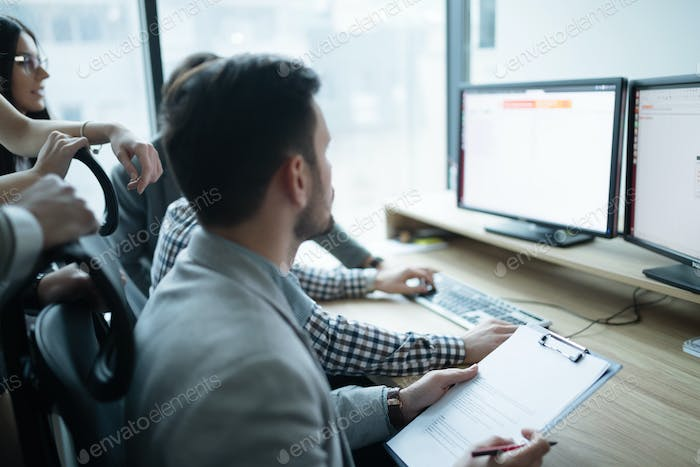Software engineers working in office on project together
