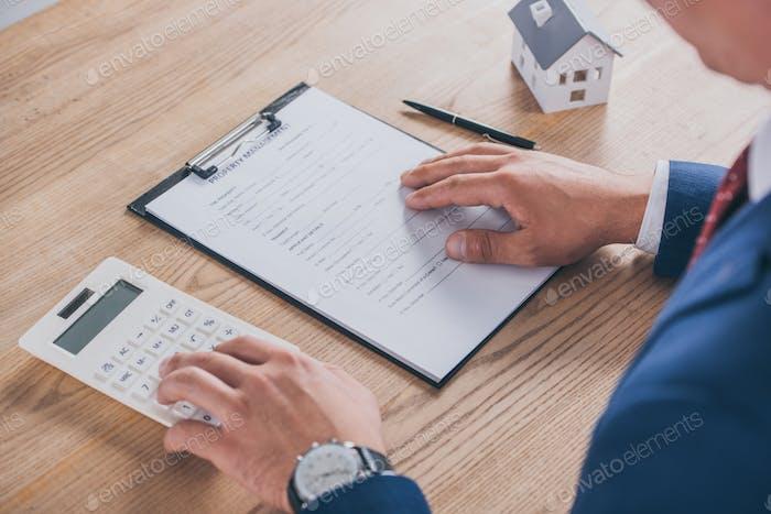 beschnittene Ansicht eines Geschäftsmannes, der eine Eigentumsvereinbarung liest und einen Taschenrechn