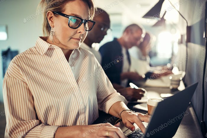 Focused mature designer working with a laptop in an office