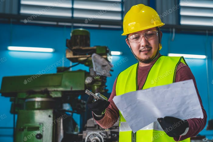 Asian machinist in safety suit checking the part of equipment with specification paper