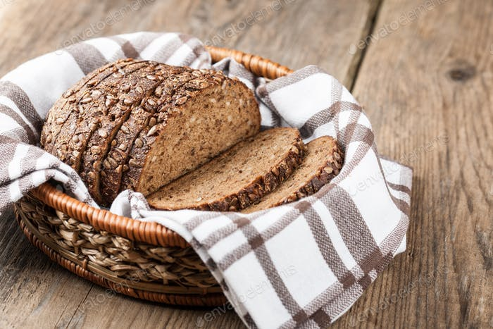 Rye bread with seeds in the basket on a wooden table