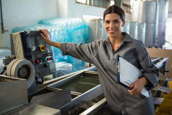 Frau mit Klemmbrett stehend in der Nähe von Maschine