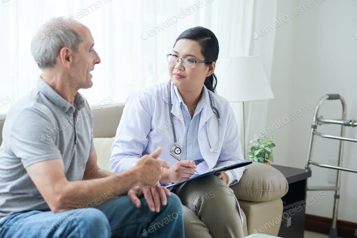 Doctor talking to senior client at home