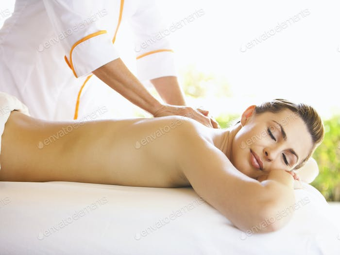 Smiling Woman with eyes closed receiving massage therapy at a luxury resort and spa