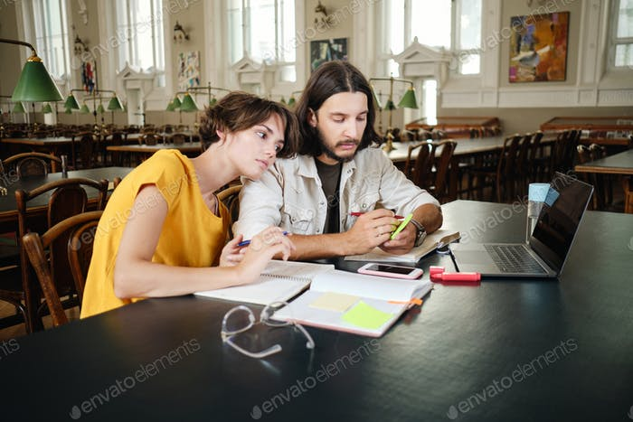 Couple of pensive students tiredly making notes studying together in library of university