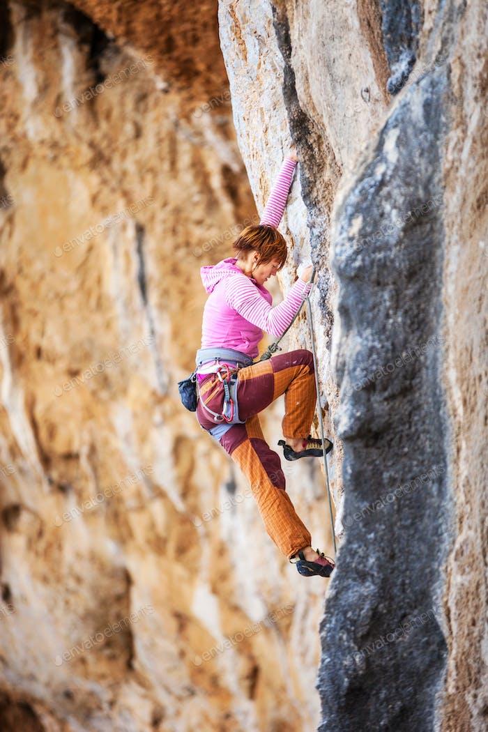 Junge weibliche Felsklettererin auf einer Klippe Gesicht