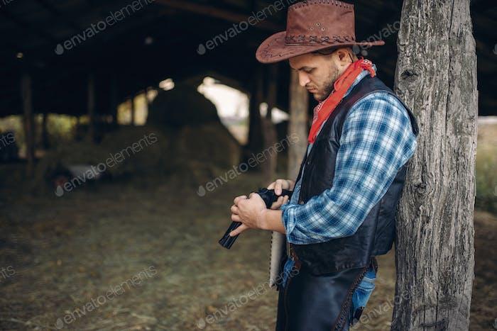 Brutal cowboy checks his revolver before gunfight