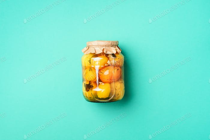 Pickled tomatoes in jar on blue background. Top view. Flat lay. Copy space. Canned and preserved