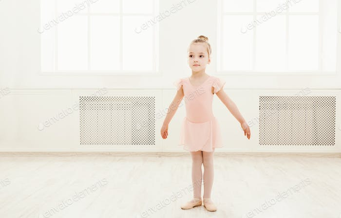 Little cute ballerina exercising in ballet costume