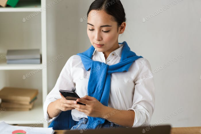 Image of asian woman using laptop and cellphone while working in office