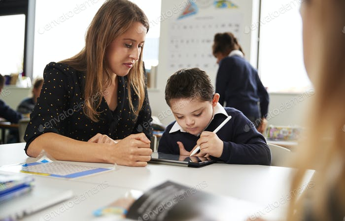 Young female teacher working with a Down syndrome schoolboy sitting at desk using a tablet computer