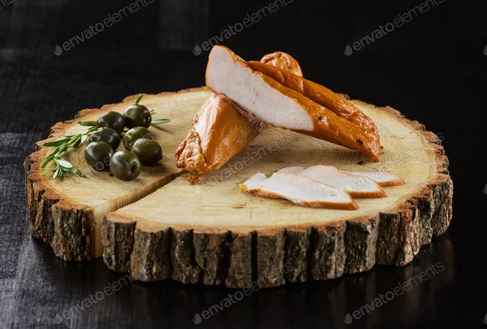 Smoked meat and olives on wooden board over black